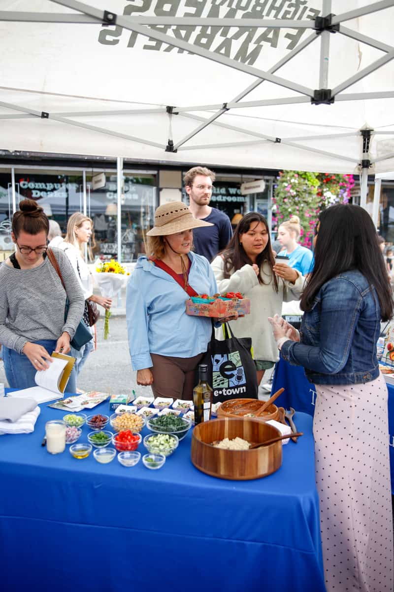 Sapana Chandra doing a cooking demo at the West Seattle Farmers Market.