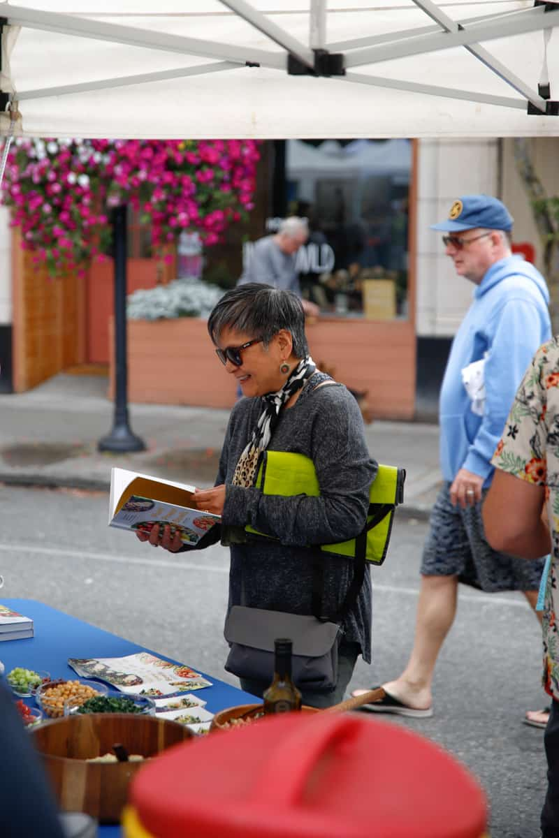 A woman at the West Seattle Farmers Market reading Plant Power Bowls.