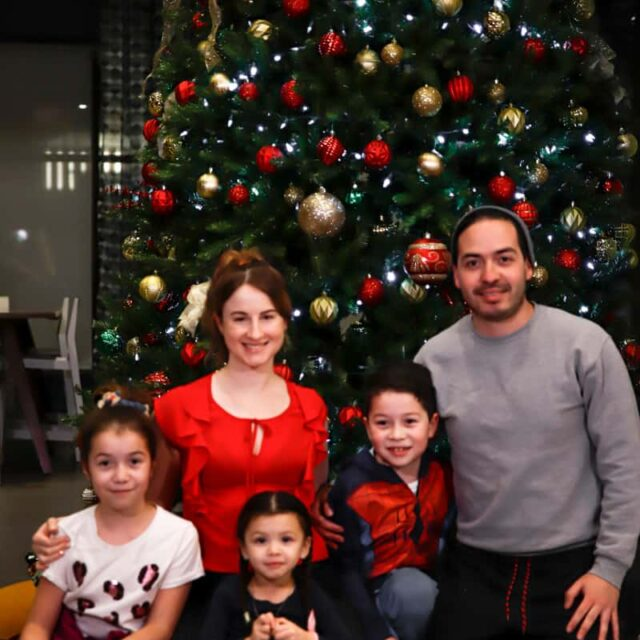 Family sitting in front of a Christmas tree.