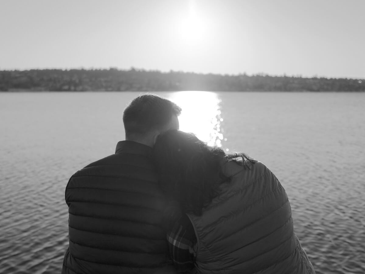 A couple sitting in front of a lake.