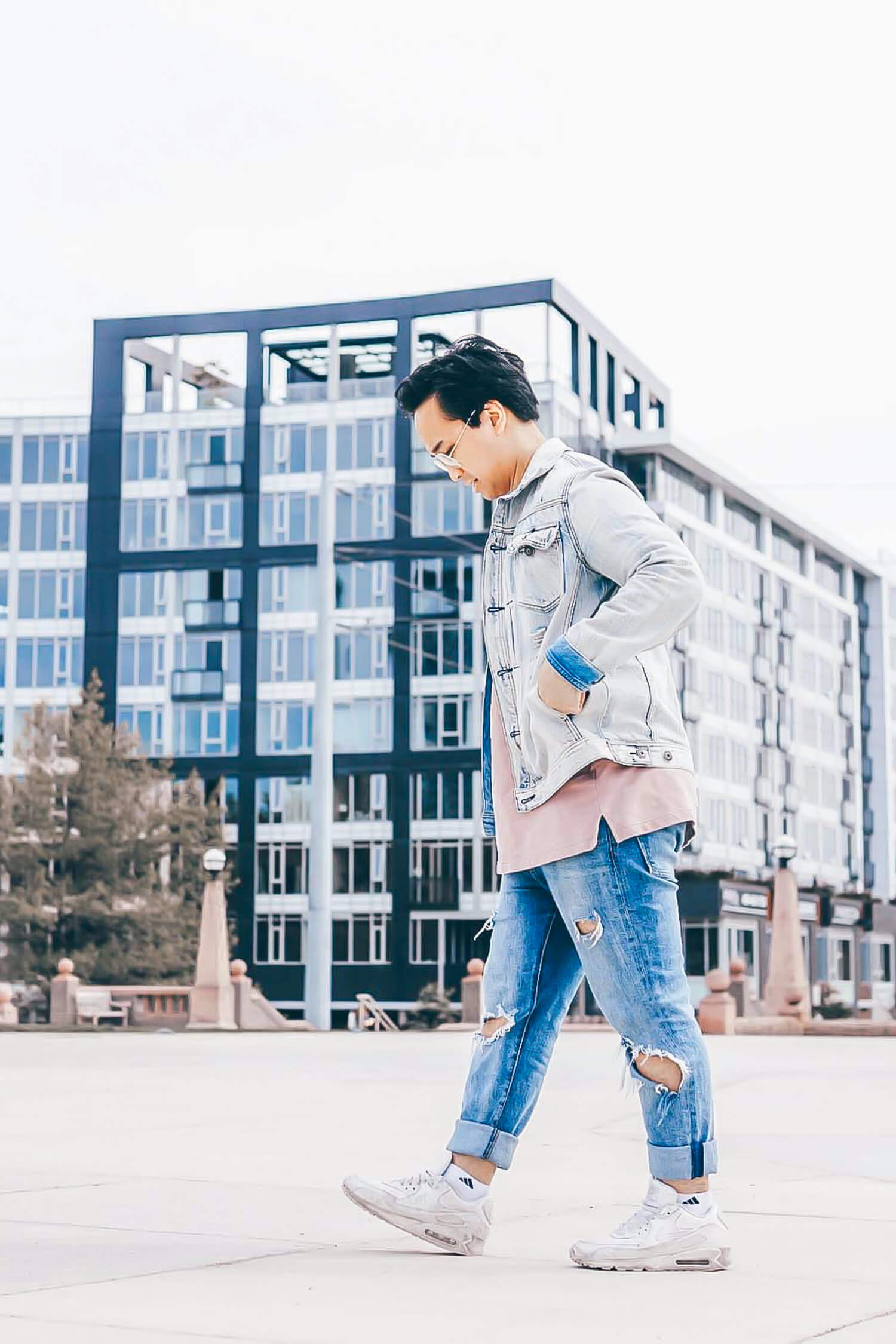 Side view of a person walking in a city park with their hands in their pocket.