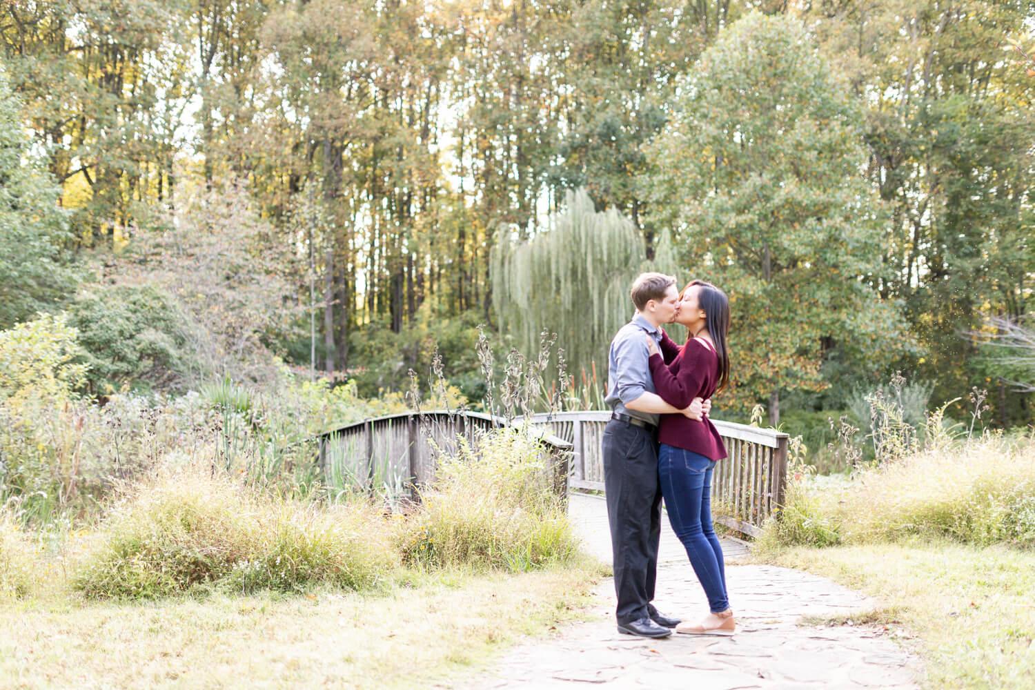 Couple kissing while standing outdoors next to a wooden bridge.
