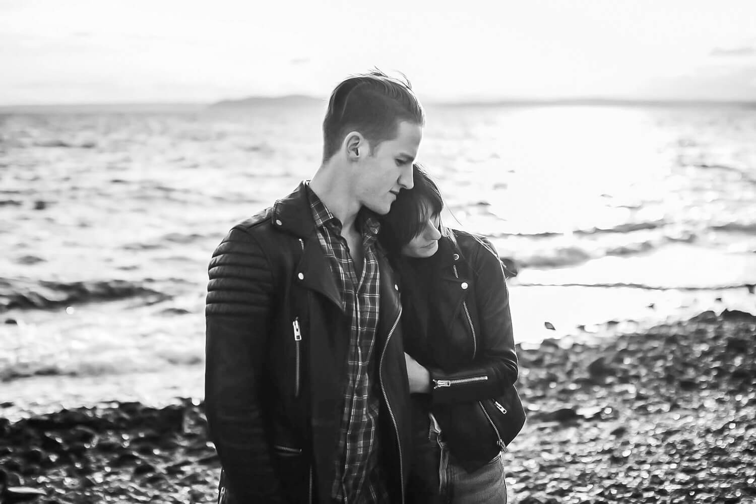 Greyscale of a couple hugging on the rocky beach with the sun behind them.